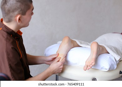 Friendly guy masseur performs well to improve condition of feet and intensively massages fingers and feet, communicates with female client, who lies on couch in light cosmetic salon. Man of European