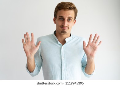 Friendly guy in white casual shirt gesturing Fine, You Won. Young Caucasian blonde man raising hands and showing palms in surrender gesture. Surrender concept