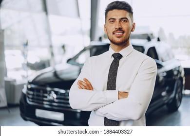 Friendly handsome car seller man standing in car salon