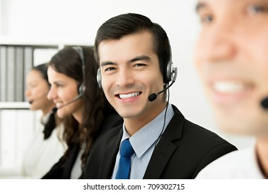 Friendly handsome hispanic man telemarketing customer service agent working in call center office with his team