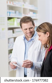 Friendly handsome male pharmacist standing explaining something on a prescription to a woman patient