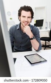 Friendly handsome young businessman sitting at his desk with his tablet-pc in front of him looking at the camera with a smile
