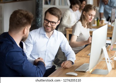 Friendly happy employee handshaking colleague at workplace thanking for help, hr or team leader shaking hand of new worker welcoming coworker starting working together at computer in office