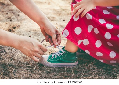 Friendly happy family. Close up loving mother helping her little daughter to tie shoelaces while spending time together, outdoor on summer day. Child in pretty red dress and green sport shoes.