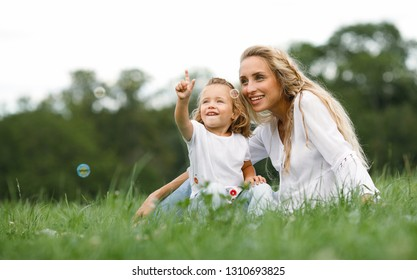 Friendly and happy family in nature.Positive and beautiful young mother and her little mischievous daughter laughing soap bubbles sitting on the grass for a walk in the park.Summer.Childhood.Lifestyle