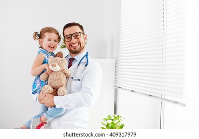 friendly happy male doctor pediatrician with patient child girl in his office at the clinic