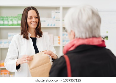 Friendly happy pharmacist dispensing medicine to an elderly woman patient placing the medication into a brown paper bag
