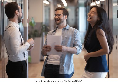 Friendly happy three diverse colleagues talking laughing at work break standing in modern office hallway, cheerful multicultural business team people having fun joking together in company hall space