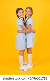 Friendly hug. Beautiful schoolgirls best friends. Back to school concept. Cute schoolgirls. Girls braided hairstyle. Cheerful schoolgirls yellow background. Little girls playing with cute braids.