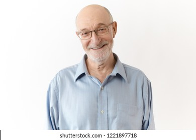 Friendly humorous grandpa with white beard smiling joyfully at camera. Elegant neat elderly businessman in glasses, rejoicing at successful effective work results, posing isolated in studio