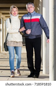 Friendly husband and wife are walking together clear sunny day between columns