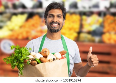 Friendly indian male supermarket or hypermarket employee holding brown paper grocery bag with thumb up as like gesture