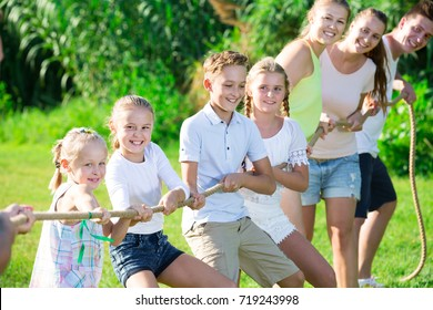 Friendly Kids With Moms And Dads Playing Tug Of War During Joint Outdoors Games On Sunny