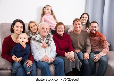 Friendly large family making numerous photos during family dinner. Focus on elderly man