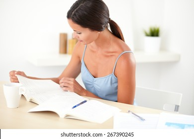 Friendly latin female in blue blouse reading a books in her room