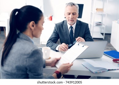 Friendly looking entrepreneur listening to young employee at office