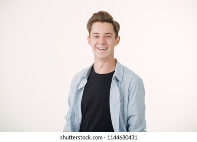 Friendly looking handsome young man wearing blue shirt smiling standing over white background