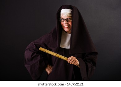 A friendly looking nun holding a ruler