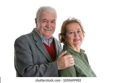Friendly looking senior couple portrait isolated on white background, where grey-haired old man holding elderly woman by her shoulders. Both looking at camera and smiling