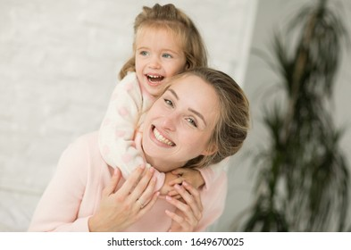 Friendly and loving family.  Emotional portrait of a happy and positive beautiful young mother and her little daughter playing on the bed in the bedroom. Happy childhood. Positive emotions.