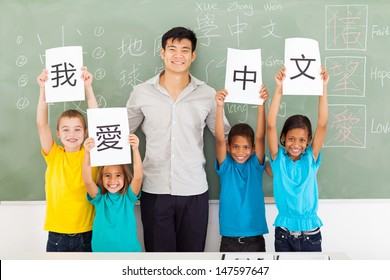 friendly male chinese teacher with group multiracial primary students holding papers saying i love chinese