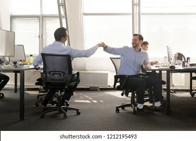 Friendly male coworker buddies fist bumping at work celebrate good teamwork result, happy smiling colleagues share success motivated by great relations, corporate culture help support respect concept