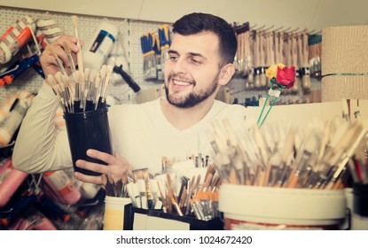 friendly male customer examining various types of brushes in paint supplies store