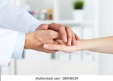 Friendly male doctor's hands holding female patient's hand for encouragement and empathy. Partnership, trust and medical ethics concept. Bad news lessening and support. Patient cheering and support
