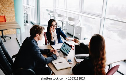 Friendly male and female colleagues having productive working process in office helping each other cooperating on research, woman giving book to partner discussing information at desktop together