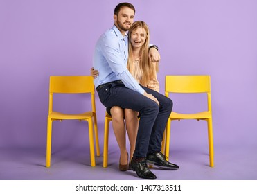 Friendly male and female colleagues having fun, laughing and playing. Young man sitting on woman's lap, looking in camera and waiting for job interview