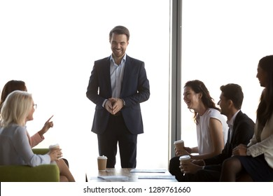 Friendly male leader having fun conversation with office workers chatting laughing talking to diverse multi-ethnic happy business people at group corporate meeting coffee break, team good relations