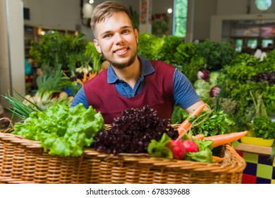 A friendly male seller posing with a huge basket of vegetables. Fresh vegetables in the background.