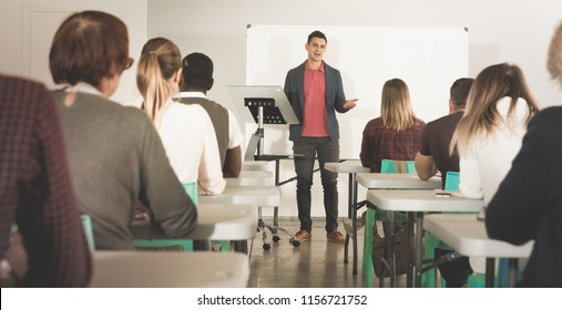 Friendly male teacher lecturing to attentive adult students at auditorium
