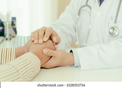Friendly man doctor hands holding patient hand sitting at the desk for encouragement, empathy, cheering and support while medical examination. Bad news lessening, trust and ethics concept