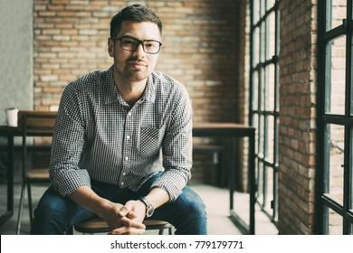 Friendly Man Sitting at Window in Loft Cafe
