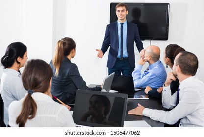 Friendly  manager making speech during business meeting in office