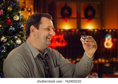 Friendly mature man makes a toast for Christmas. Side portrait of cheerful man holding vodka shot  with left hand. He wearing gray striped shirt and tie sits in cafe on holiday blurred  background
