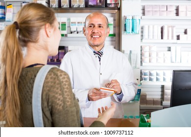 Friendly mature pharmacist serving young woman in pharmacy