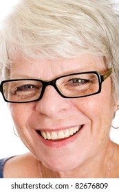 Friendly, mature white haired woman with glasses and a smile.