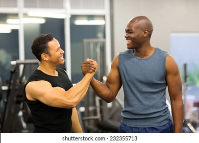 friendly men handshaking in gym