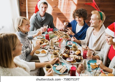 Friendly men and women in xmas wear gathered by festive table