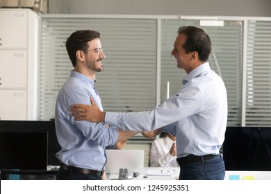 Friendly middle aged boss handshaking male successful employee, congratulate confident worker with promotion, business achievement, thank for good work results, expressing respect, rewarding