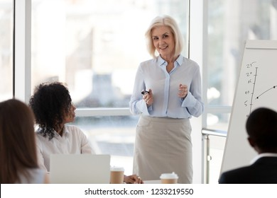 Friendly middle aged female leader mentor presenting financial graph on flipchart, mature business coach speaking at team meeting training staff group explains corporate business plan project report