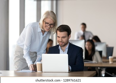 Friendly middle aged female mentor executive training employee in office helping with computer work, smiling old corporate manager supervise motivating teaching new worker colleague looking at laptop