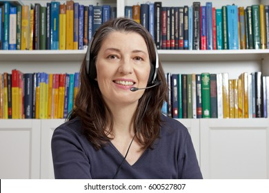 Friendly middle aged woman with blue t-shirt and head set in an office with lots of books having an live video call via the internet, telelearning, e-education