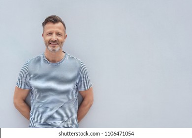 Friendly middle-aged man posing against a textured white wall smiling at the camera with copy space