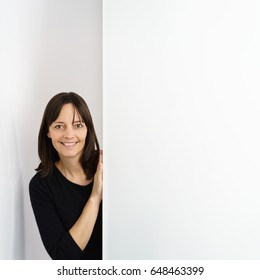 Friendly middle-aged woman peering around a white door with copy space smiling happily at the camera
