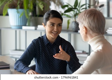 Friendly millennial indian businesswoman talking to blonde female colleague, sitting at table in office. Two young multiracial employees discussing working issues or enjoying informal conversation.