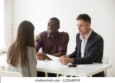 Friendly multiethnic hr team talking to female job candidate, reading her resume considering applicant candidature, workers excited liking employee, laughing at joke. Recruitment, hiring concept