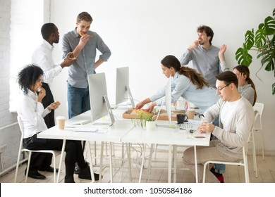 Friendly multi-ethnic team having lunch together eating pizza in office, multiracial employees talking sharing meal during corporate break, diverse staff people group enjoy italian food at workplace